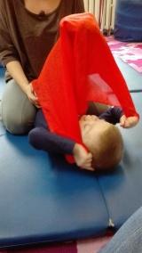 Integracja ciała z użyciem chusty. Adaś naciąga ją stopami i dodatkowo unosi głowę...